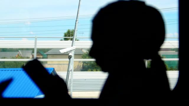 silhuetten av muslimska kvinnor tittar på telefonen, under tågresan - anständig klädsel bildbanksvideor och videomaterial från bakom kulisserna