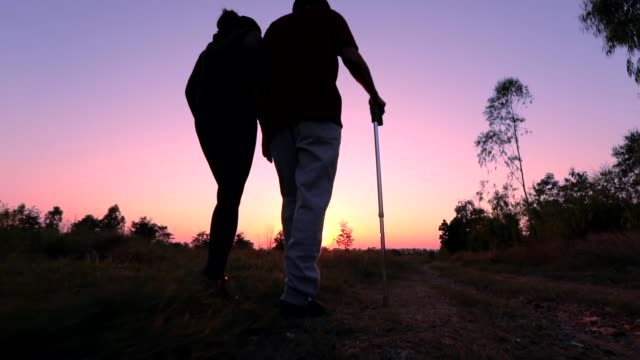 Silhouette of old man using staff walking with his daughter during sunset, Concept a Rehabilitation after injury, slow motion
