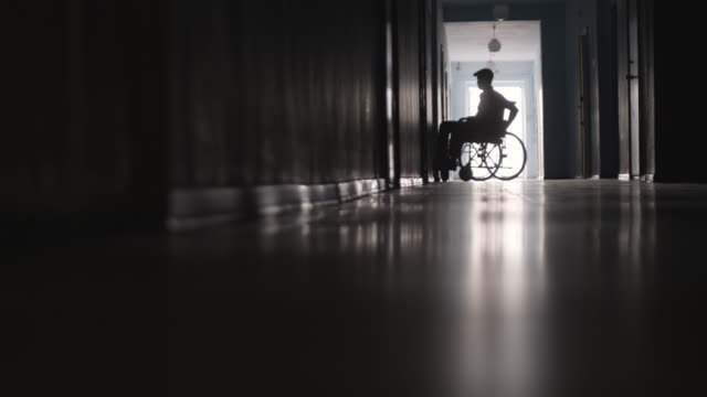Silhouette of Paraplegic Patient Riding Wheelchair along Hospital Corridor Silhouette of disabled man leaving hospital ward and riding wheelchair along dark hallway wheelchair stock videos & royalty-free footage