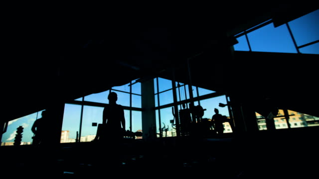 Silhouette of people doing exercise in fitness club and gym center ビデオ