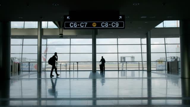 stockvideo's en b-roll-footage met silhouet van mensen in de luchthaventerminal wandelen met bagage - vliegveld vertrekhal
