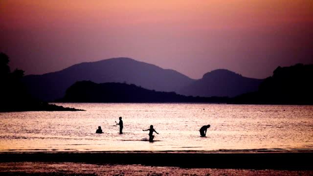 silueta de personas jugando en la playa - vídeo