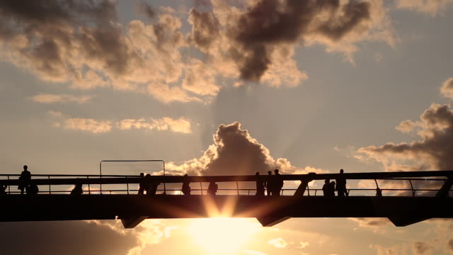 Silhouette Of People Walking On London Millennium Footbridge At Sunset