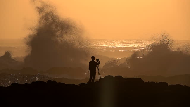 Silhouette of Photographer and Slow Motion of Raging Ocean Waves Crashing Rocks during Sunset video