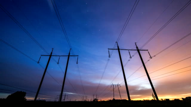 Silhouette of power lines begin on the background of beautiful sunset sky and end on the background of starry sky with Big Dipper constellation. video