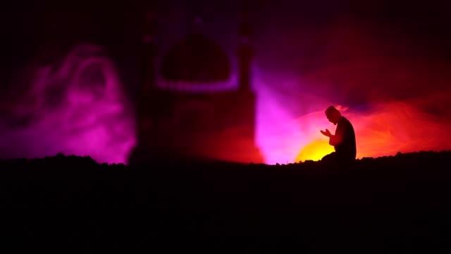 Silhueta do homem a rezar com turva Mesquita edifício em fundo nebuloso tonificado. Fundo de Ramadan Kareem. Decoração do feriado de Eid muçulmano. Conceito de religião as pessoas a rezar. Foco seletivo - vídeo