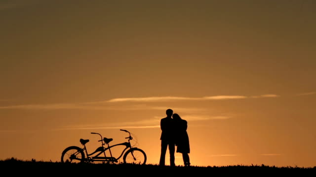 Silhouette of  Romantic Couple With Tandem Bicycles Watching And Enjoyig The Sunset  Leaning Together