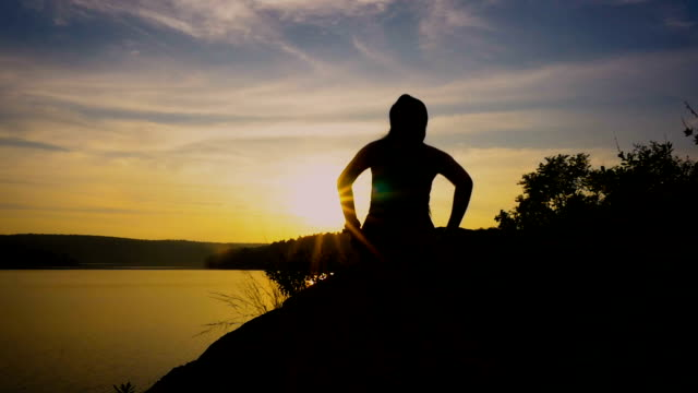 Silhouette of runner woman athlete training outdoors exercising celebrating arms up on mountain at sunset or Success, winning and achievement concept video