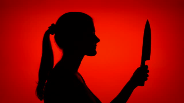 silhouette of scary woman holding sharp blade. female's face in profile with knife on red background - lama oggetto creato dall'uomo video stock e b–roll