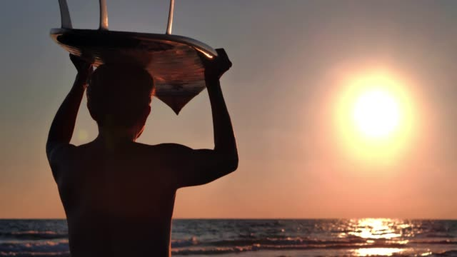Silhouette of senior man carrying surfboard on head at beach during sunset.Real Bodies