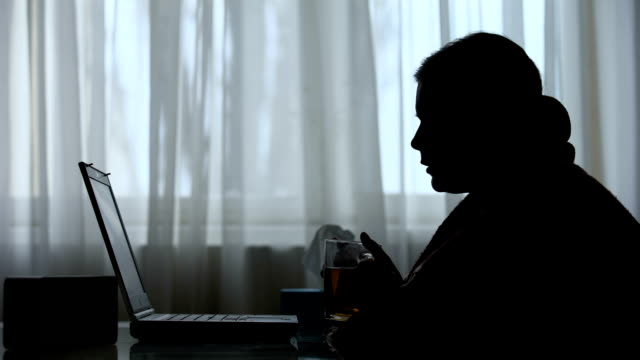 Silhouette of sick woman working on laptop at home late at night, deadline
