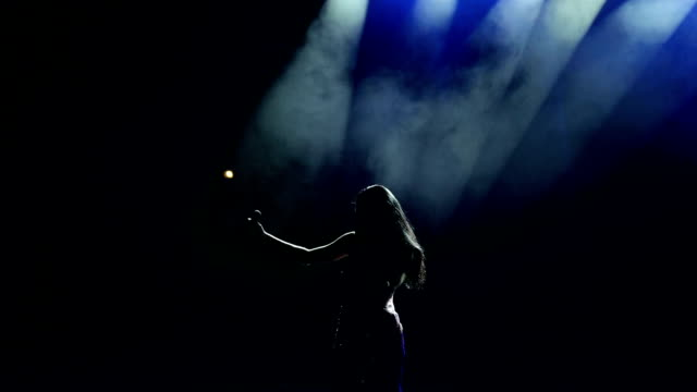 silhouette of singer on stage at smoky background. - cantante video stock e b–roll