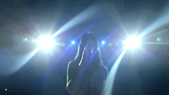 silhouette of singer on stage under the spotlights - cantante video stock e b–roll
