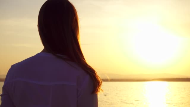 silhouette of smiling young woman at sunset on lake. female figure at golden hour in slow motion - mindfulness filmów i materiałów b-roll