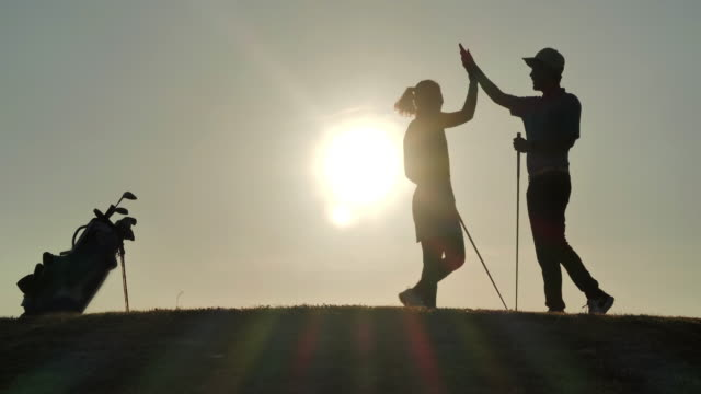 Silhouette of success golfers team on green golf field.Celebration,Success,Teamwork,Collaboration,Support,Togetherness.Confidence,Leadership,Power,Skill,Strength, Friendship,concept.Sports Cinemagraphs.Personal Trainer video