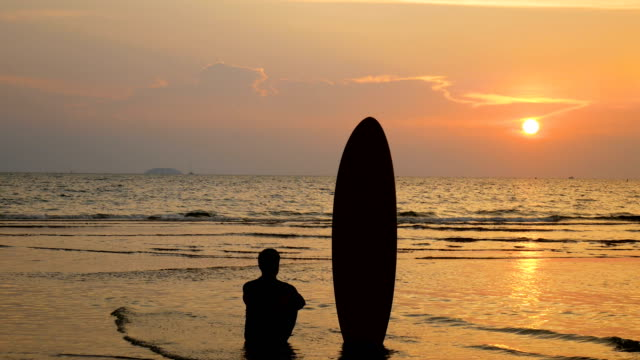 4k. silhouette of surfer man sitting on the sea beach with long surf boards at sunset on tropical beach - phuket video stock e b–roll