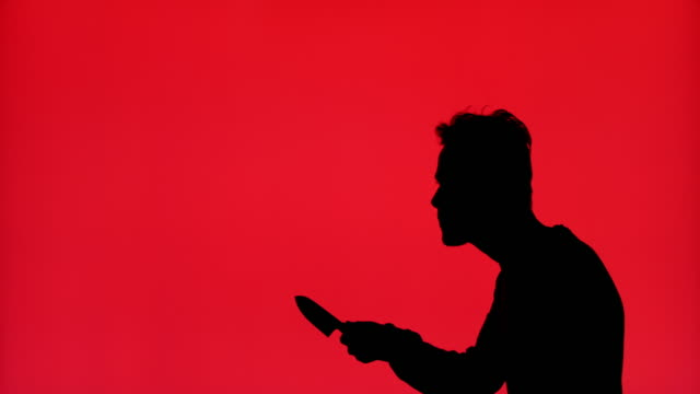 Silhouette of the man lifts his hand to stab with knife