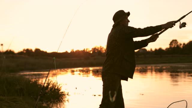 silhouette of the old fisherman on the background of a beautiful sunset. - żabnicokształtne filmów i materiałów b-roll