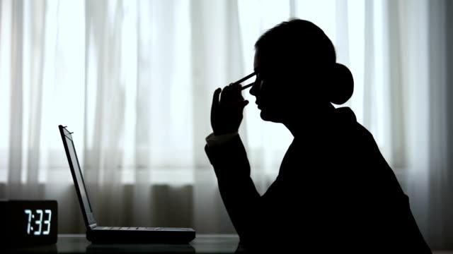 силуэт усталой женщины, заканчивающих свою ночную смену, принимая ноутбук выходя из комнаты - работа допоздна стоковые видео и кадры b-roll