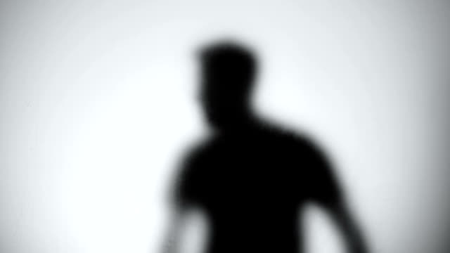 Silhouette of trapped man standing behind glass wall, room escape, close-up