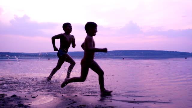 stockvideo's en b-roll-footage met silhouet van twee jongens loopt langs de oever van de rivier - rivieroever
