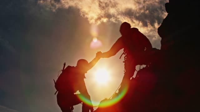 Silhouette of two mountaineers climbing the top at sunset