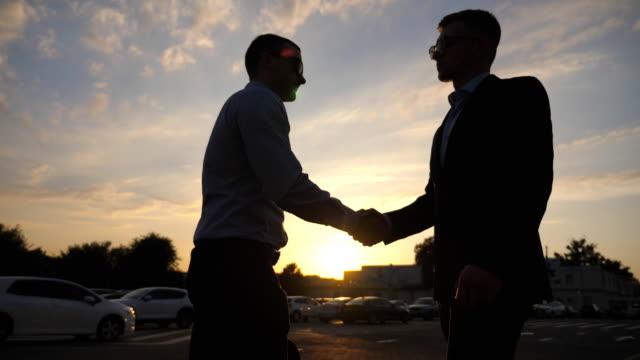 silhuetten av två unga affärsmän farväl och kramar varandra utomhus. kollegor eller business partner embracing och avvika med solen flare på bakgrunden. skilsmässan mellan goda vänner utomhus. slow motion närbild sidovy - kostym sida bildbanksvideor och videomaterial från bakom kulisserna