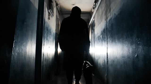 黒いジャケットを着て、長い暗い廊下でバッグを運ぶ認識できない犯罪者のシルエット。 - 犯罪者点の映像素材/bロール