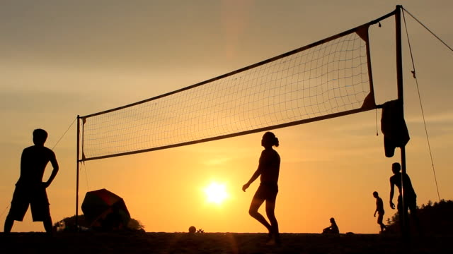 silhouette of volleyball players on the beach at sunset video
