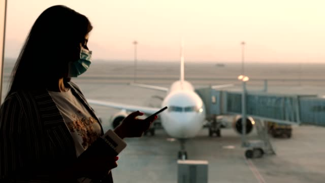 vídeos de stock e filmes b-roll de silhouette of woman in mask, uses mobile, in front of panoramic window with runway and big plane view, at airport. flights re-opened after coronavirus outbreak end. opening borders. travel open - covid flight