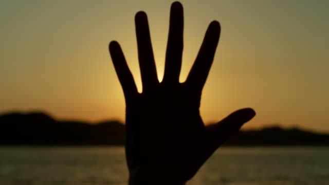太陽に対して手で女作るフレア形状のシルエット - 指点の映像素材/bロール