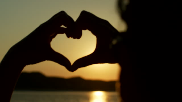 silhouette of woman making heart shape with hands against sun - vivere semplicemente video stock e b–roll
