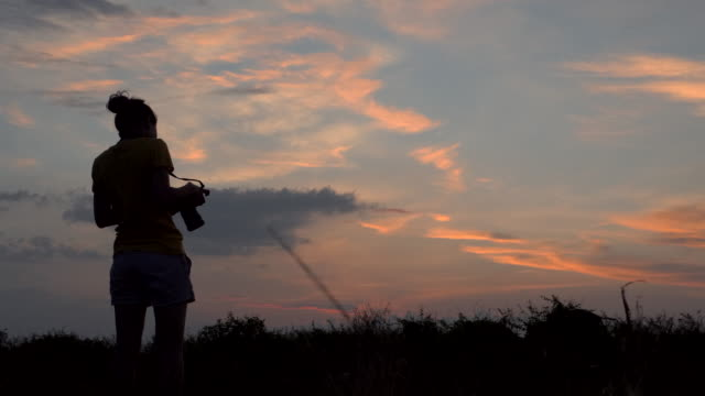 Silhouette of woman photographer