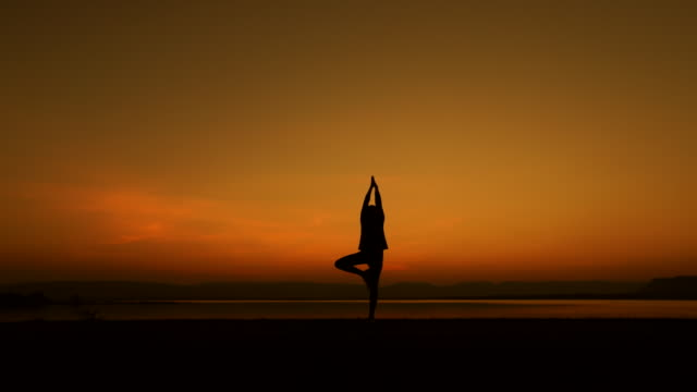 Silhouette of woman Practicing Yoga at Sunset, slow motion Video slow motion of Silhouette of woman Practicing Yoga at Sunset (HD) lotus position stock videos & royalty-free footage