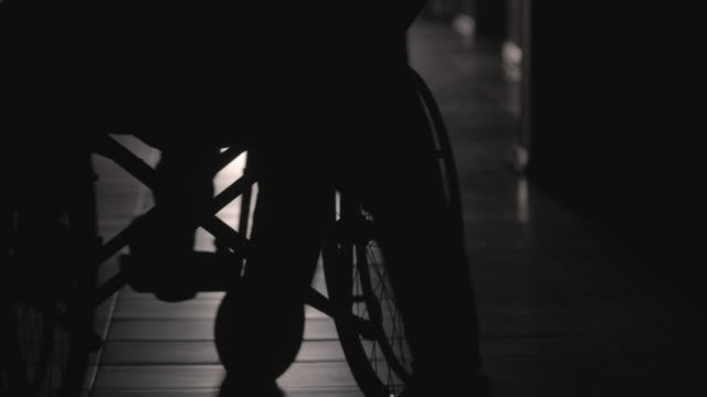 Silhouette of Woman Pushing Patient on Wheelchair along Corridor Rear view of silhouette of woman pushing disabled man on wheelchair along hallway of retirement home pushing wheelchair stock videos & royalty-free footage
