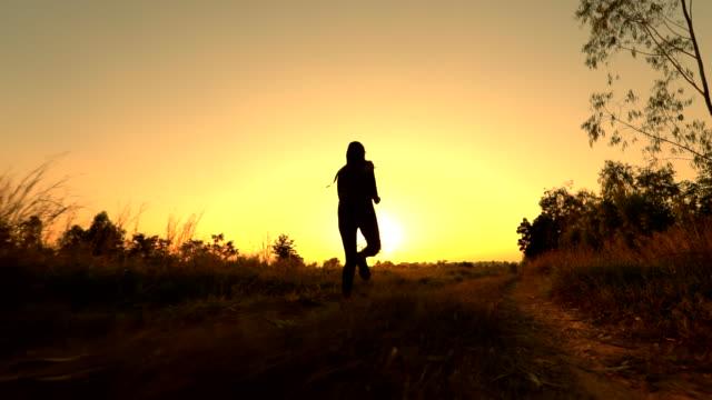 ağır çekim günbatımı, egzersiz ve sağlıklı, yavaş hareket kavramı çalışan kadın silüeti - sabah stok videoları ve detay görüntü çekimi