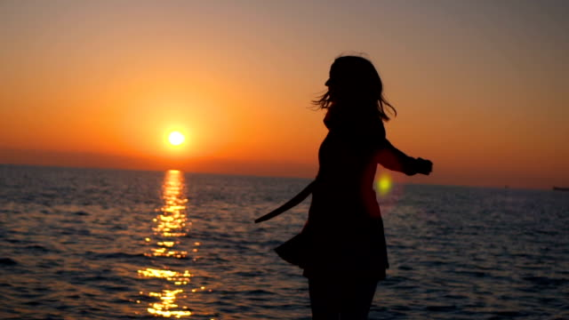 Silhouette of woman spinning at sunset video