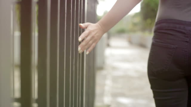 silhouette of woman walking by touching the bars of a gate video