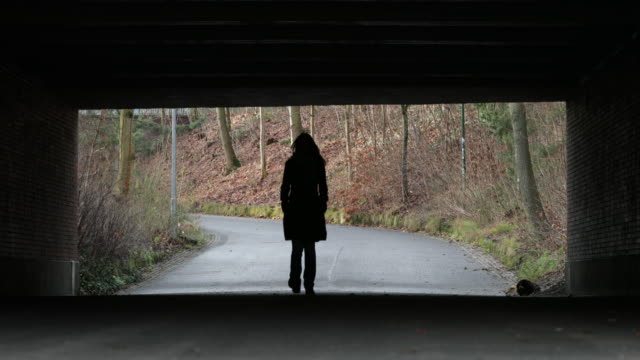 Silhouette of Woman walking under a bridge in 4K. Lonely melancholic sad atmosphere concept of destiny journey road direction