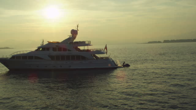 Silhouette of Yacht and Jet Ski Sunset - Helicopter shot video