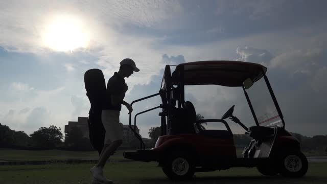 silhouette of young asian chinese man golfer unpacking equipment from golf cart at golf course