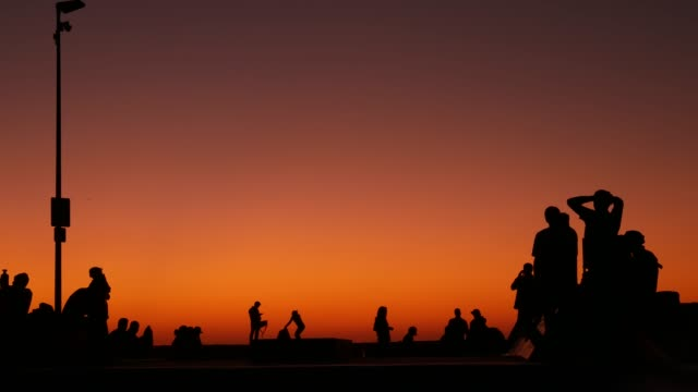 Silhouette of young jumping skateboarder riding longboard, summer sunset background. Venice Ocean Beach skatepark, Los Angeles California. Teens on skateboard ramp, extreme park. Group of teenagers.