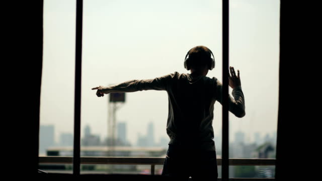 Video Silhouette of young man dancing ad listening music in wireles headphones stand on hotel room balcony