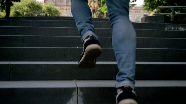 Silhouette of young man is running on stairs in park in daytime in summer, hurrying concept