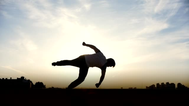 Silhouette of young man outdoors doing acrobatic elements video