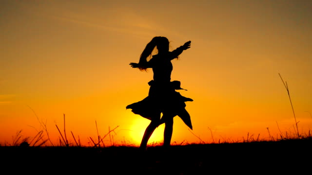 Silhouette of young witch dancing at field video