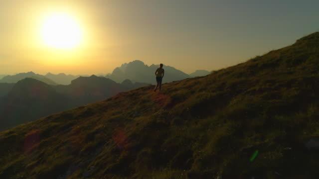 anteni̇: tırmanma ve gün batımında dağın ulaşan genç kadın silüeti. - patika stok videoları ve detay görüntü çekimi
