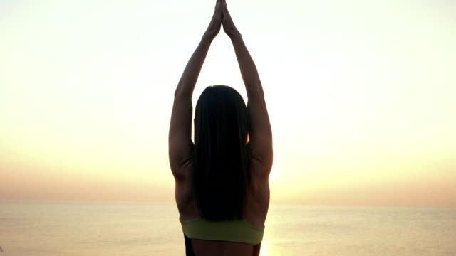 Silhouette of young woman in bodysuit practicing yoga on the beach above sea at amazing sunrise. Suria Namaskar. Fitness, sport, yoga and healthy lifestyle concept. Slow motion video