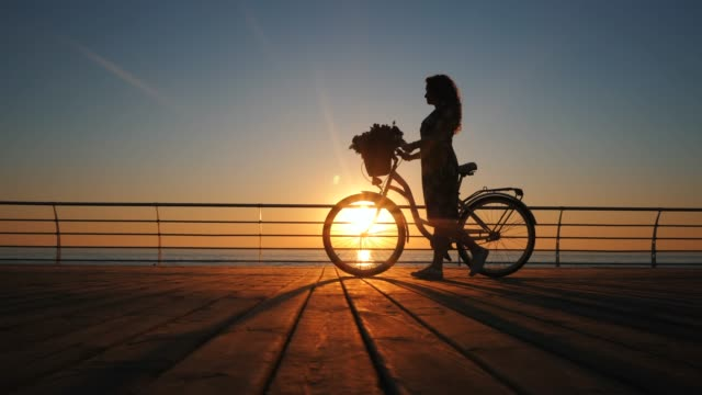 Silhouette of young woman in dress with vintage bicycle and bouquet of flowers walking on wooden embankment near sea during sunrise or sunset. Romantic travel concept. Beautiful scene