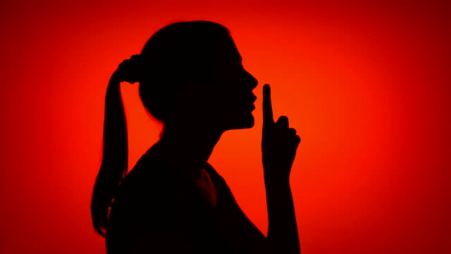 vídeos y material grabado en eventos de stock de silueta del gesto de silencio que hace de mujer joven sobre fondo rojo. concepto de misterio y secreto - dedo sobre labios